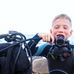 cheerful boy with blond hair breathes through a diving balloon